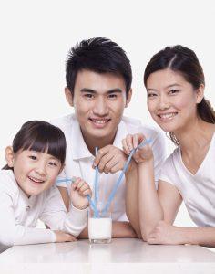 Family sharing a glass of milk, studio shot